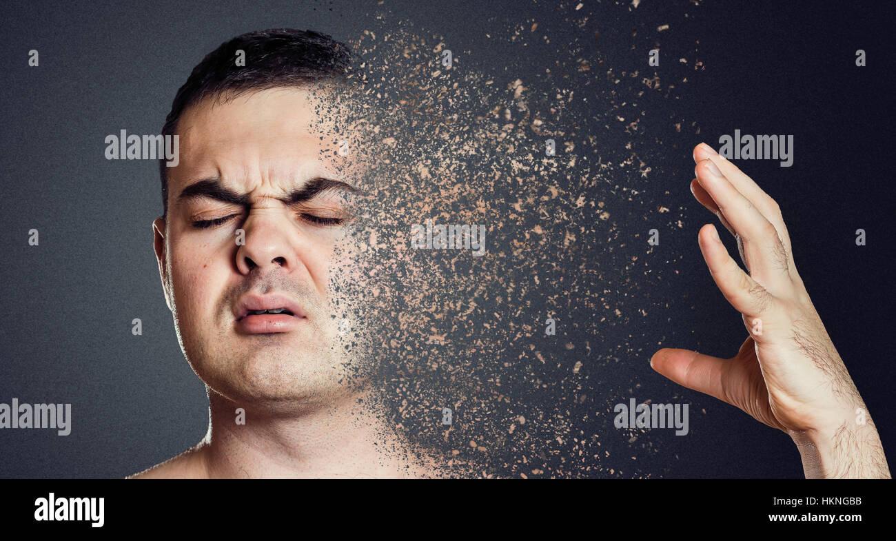 Depressive man dissolving his face into pieces. Mental health concept. - Stock Image