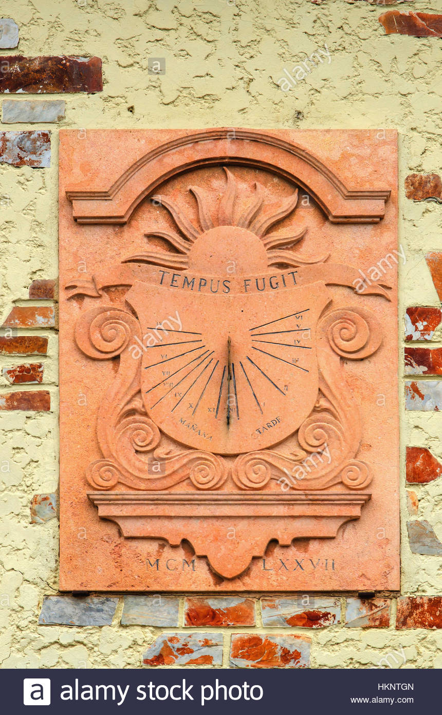 Traditional sundial or sun clock in a wall. Tempus fugit - Stock Image