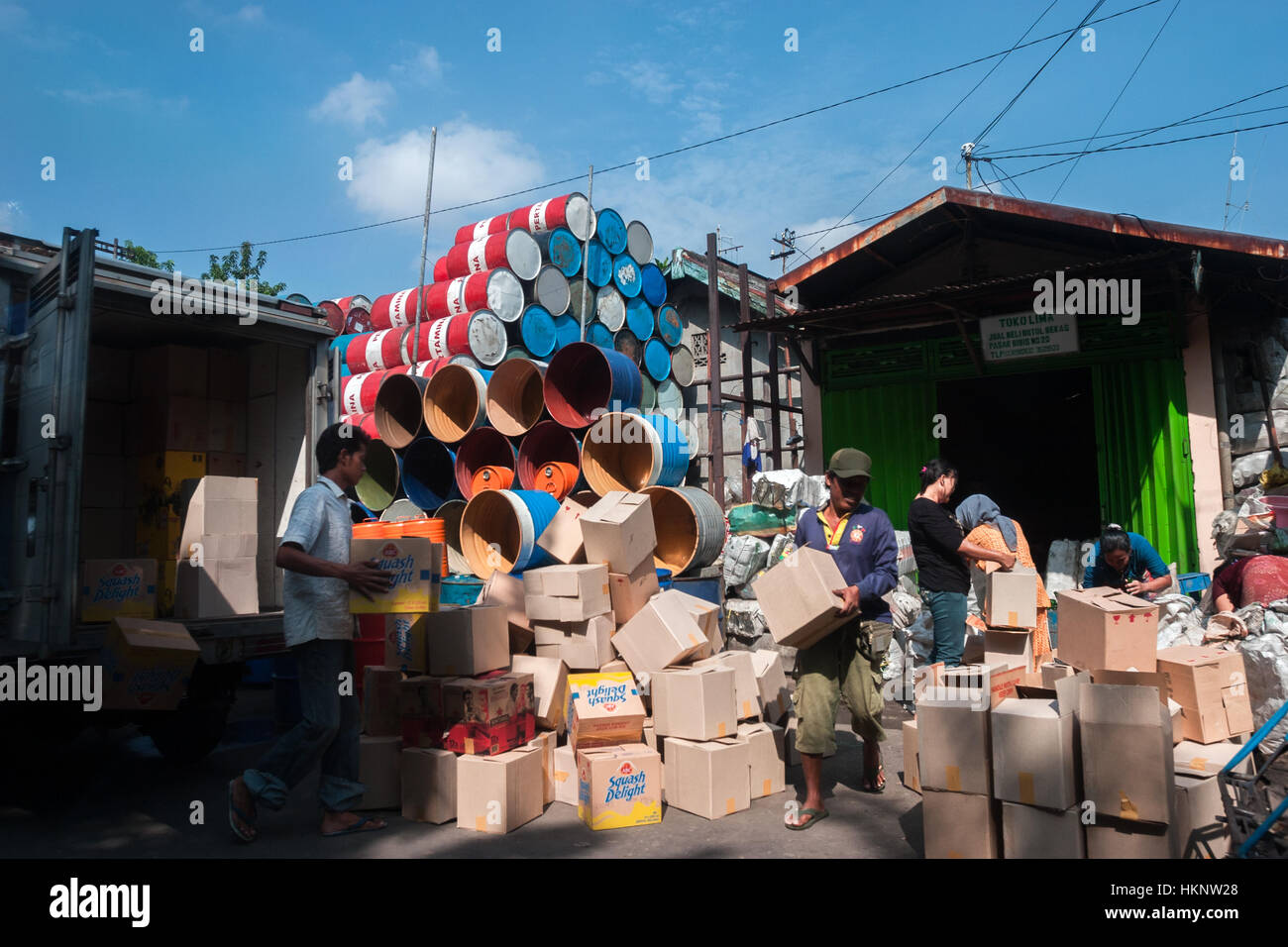 Workers activity in a reseller's storage of used packaging items in Surabaya, Indonesia. - Stock Image