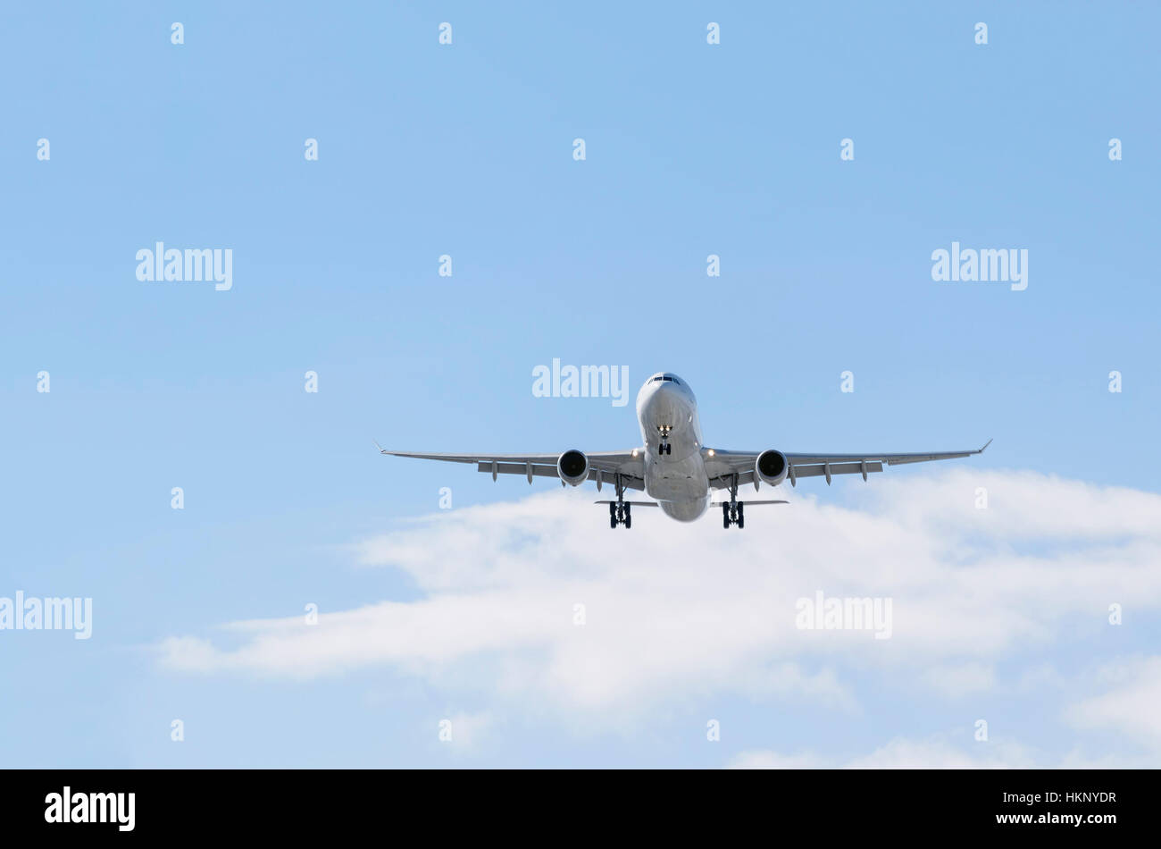 Airplane Airbus A330, of Iberia airline. Blue sky with some clouds. - Stock Image