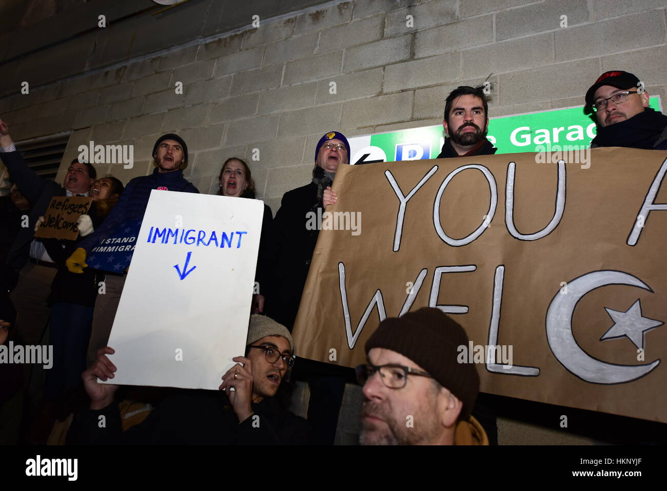 Members of NY City Council stand against wall with banner. Thousands gathered at Terminal Four at JFK Airport to Stock Photo