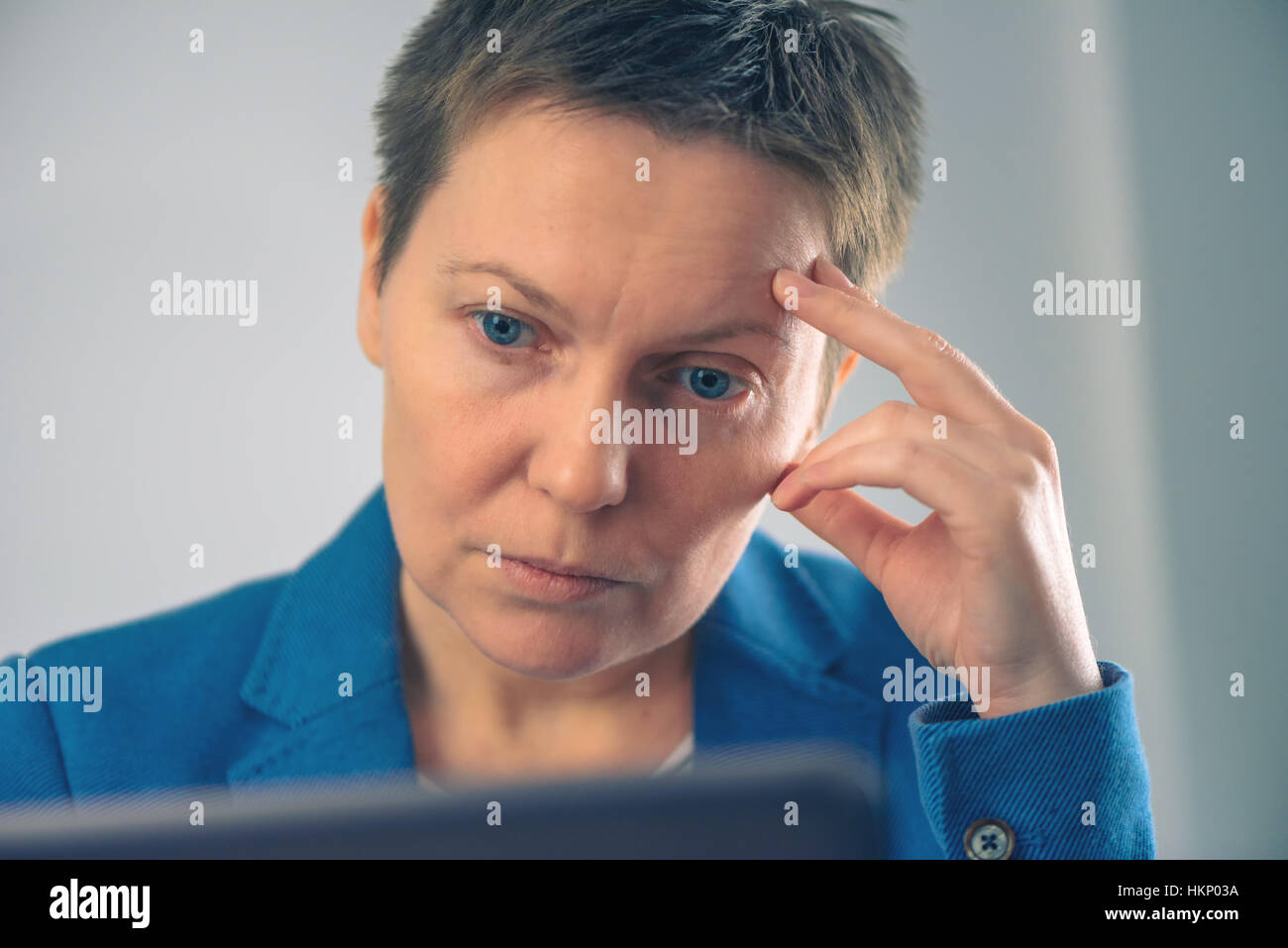 Disappointed businesswoman looking at business results on laptop screen in the office - Stock Image