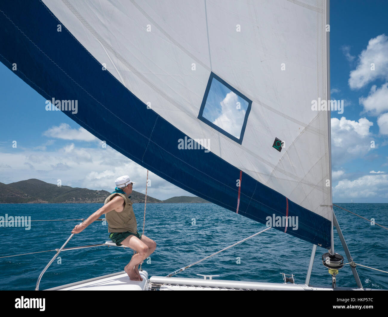 Sailor sits on the corner of the trampoline deck under full sail off the British Virgin Islands. - Stock Image