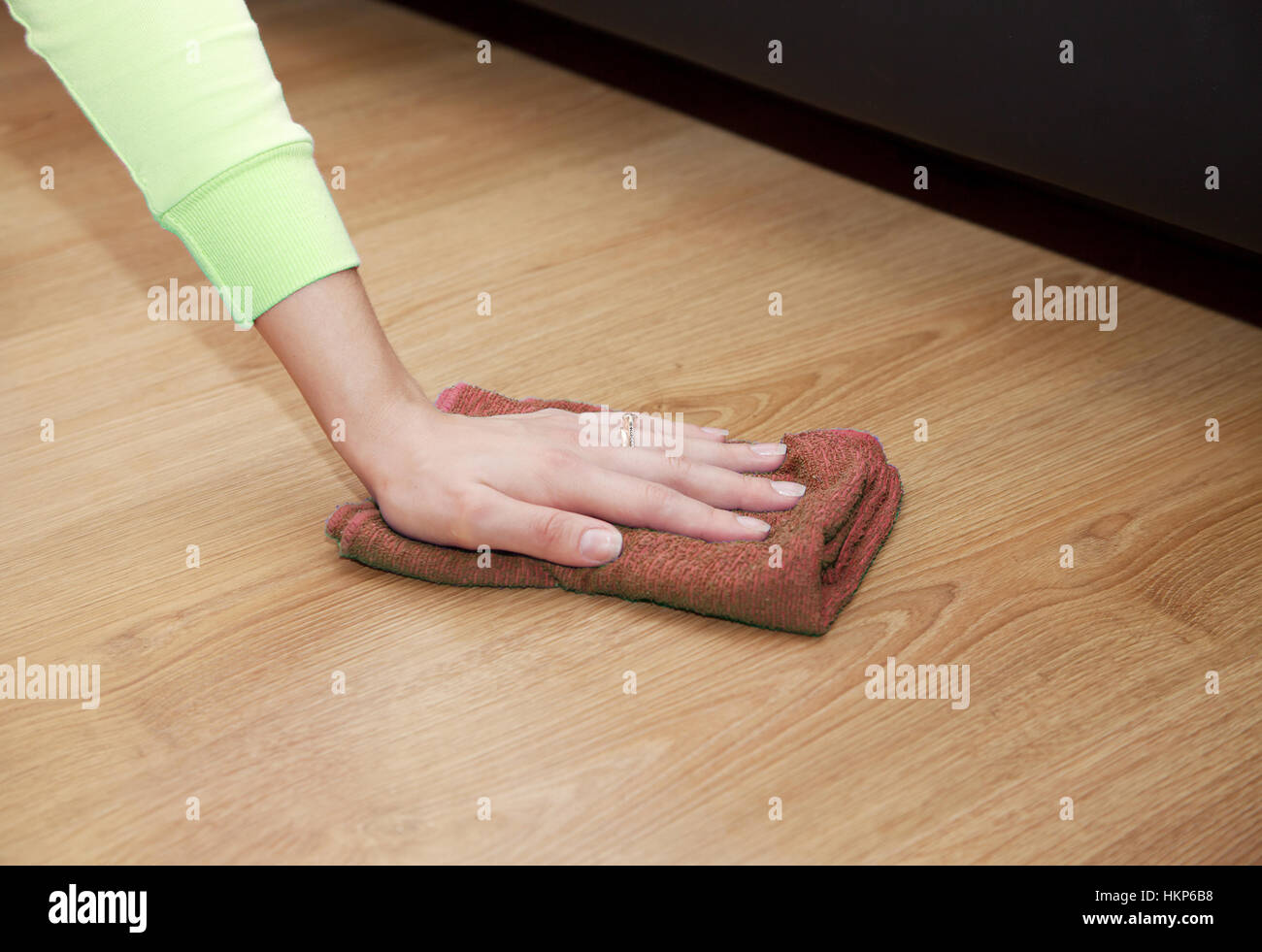 woman's hand cleaning the wooden floor with a brown floorcloth closeup - Stock Image