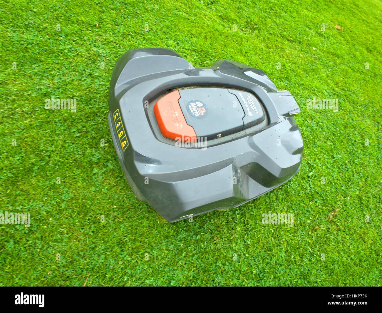 Husqvarna automower cutting lawn - Stock Image
