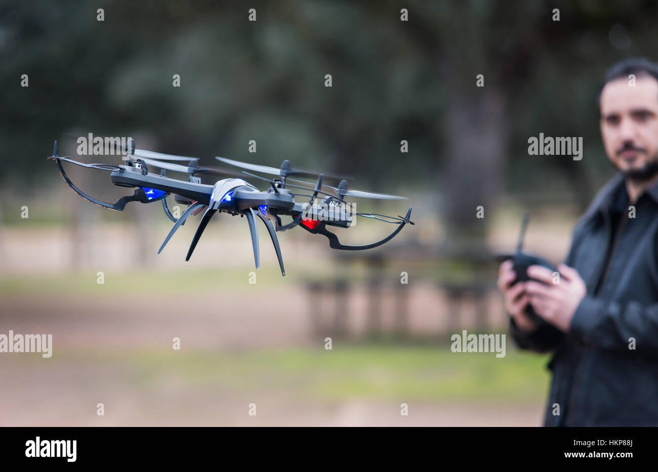 A man Operating The Drone By Remote Control In The Park - Stock Image
