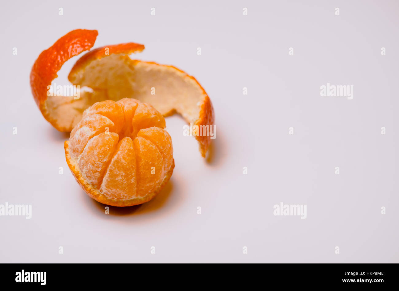 A single whole fresh clementine isolated on white background with room for text or copy. - Stock Image