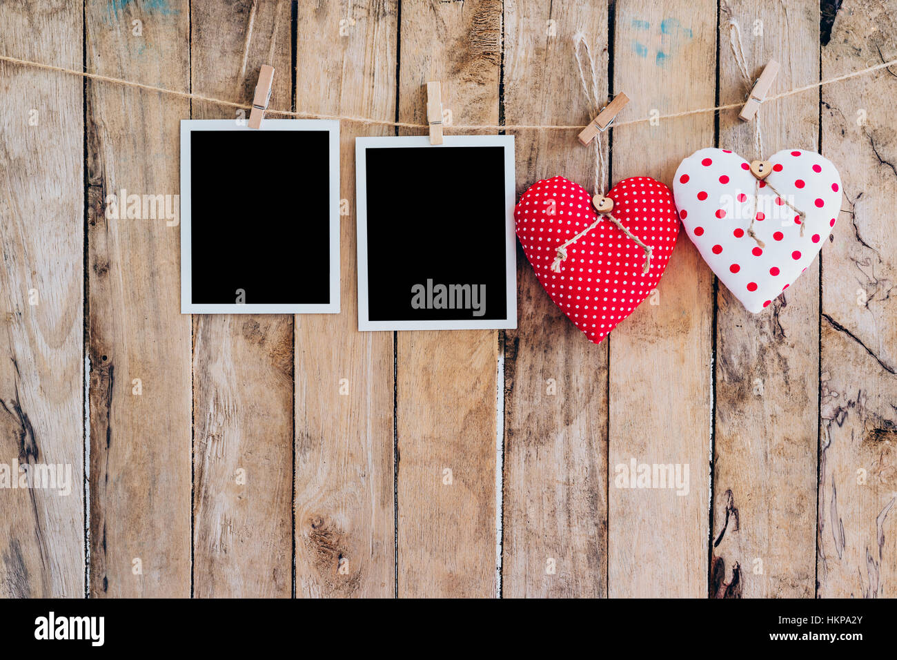 Two heart and two photo frame hanging on clothesline rope with ...