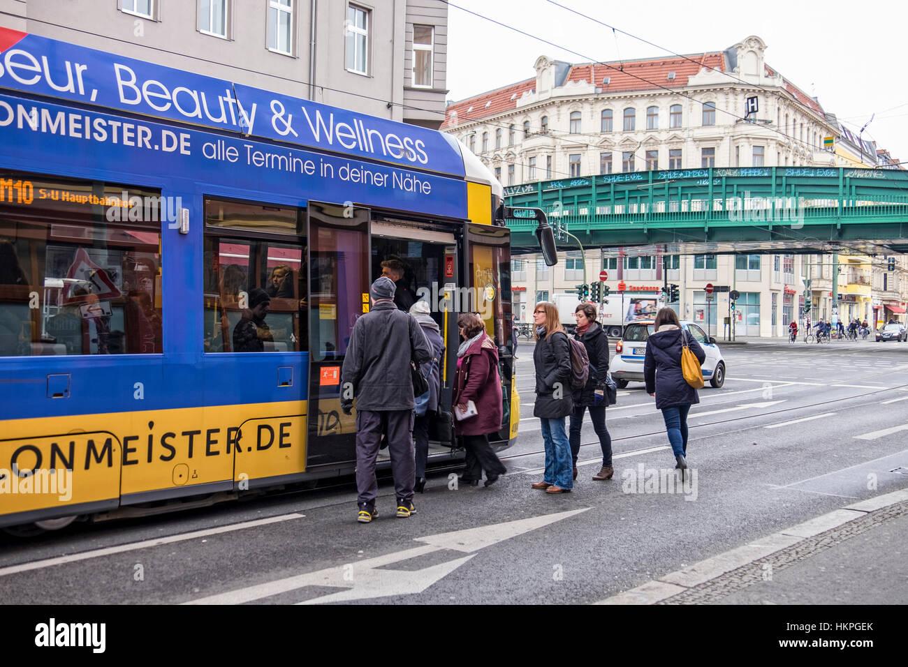 Berlin, Prenzlauer Berg, People boarding stationary tram in Berlin street. - Stock Image
