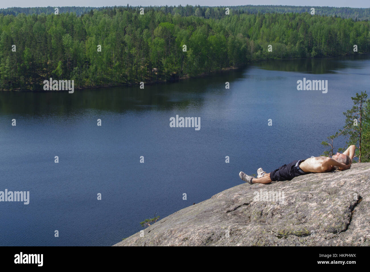 a happy young man laying on a rocky slope above a lake - Stock Image