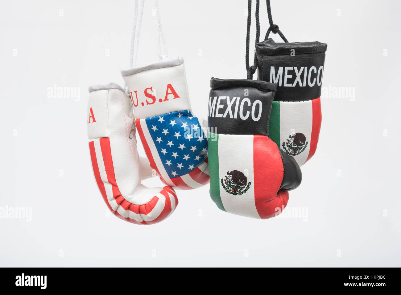 America-Mexico stand-off (Donald Trump) represented by hanging USA and Mexican emblem boxing gloves. NAFTA breakdown - Stock Image