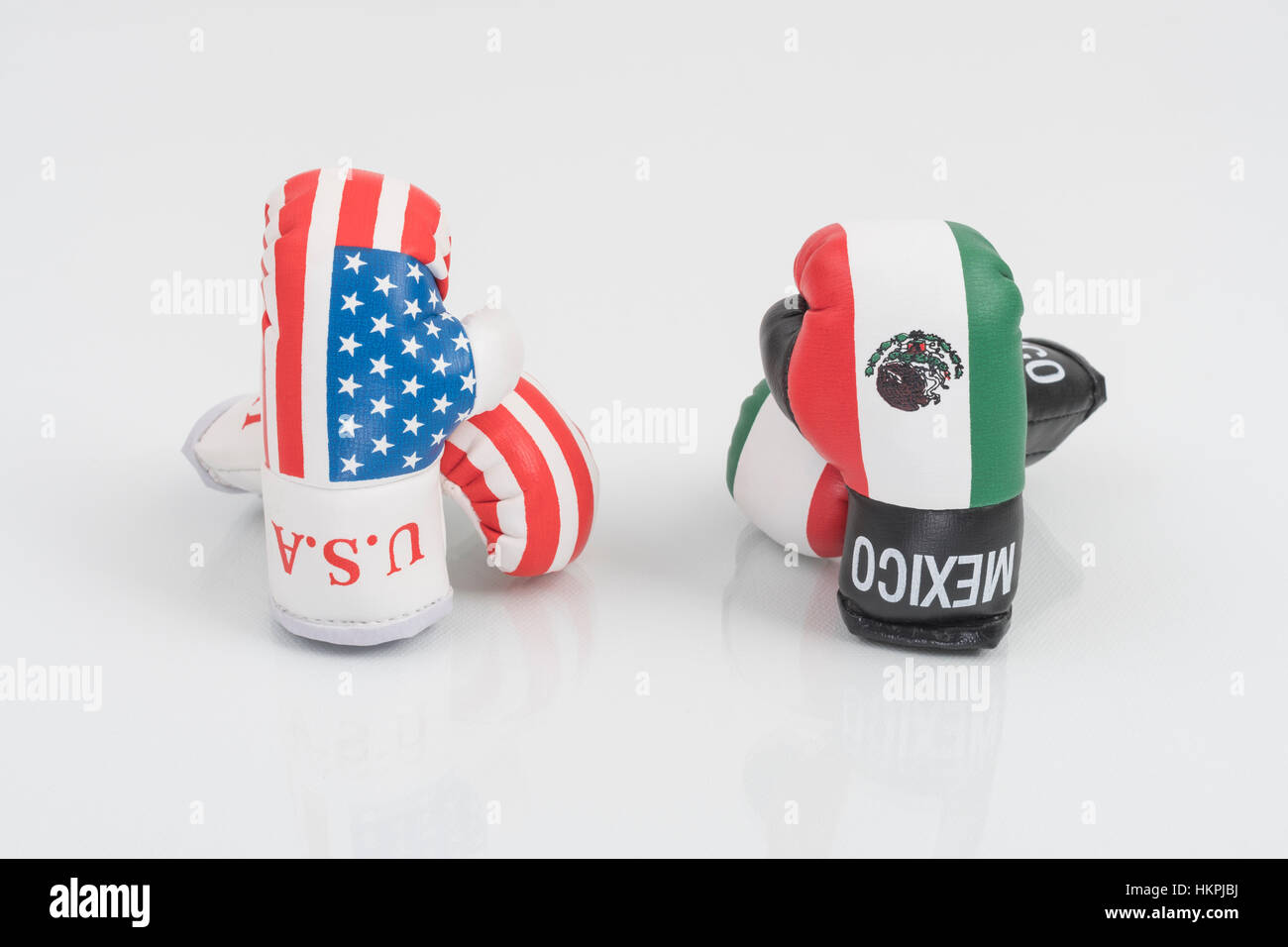 America-Mexico stand-off (Donald Trump) represented by USA and Mexican emblem boxing gloves. NAFTA breakdown concept. - Stock Image