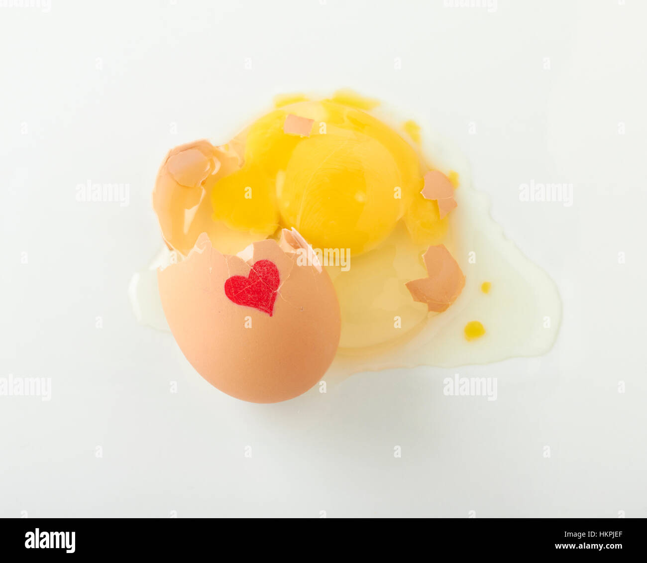 A cracked raw brown egg with a drawn red heart is spilling onto a white surface. - Stock Image