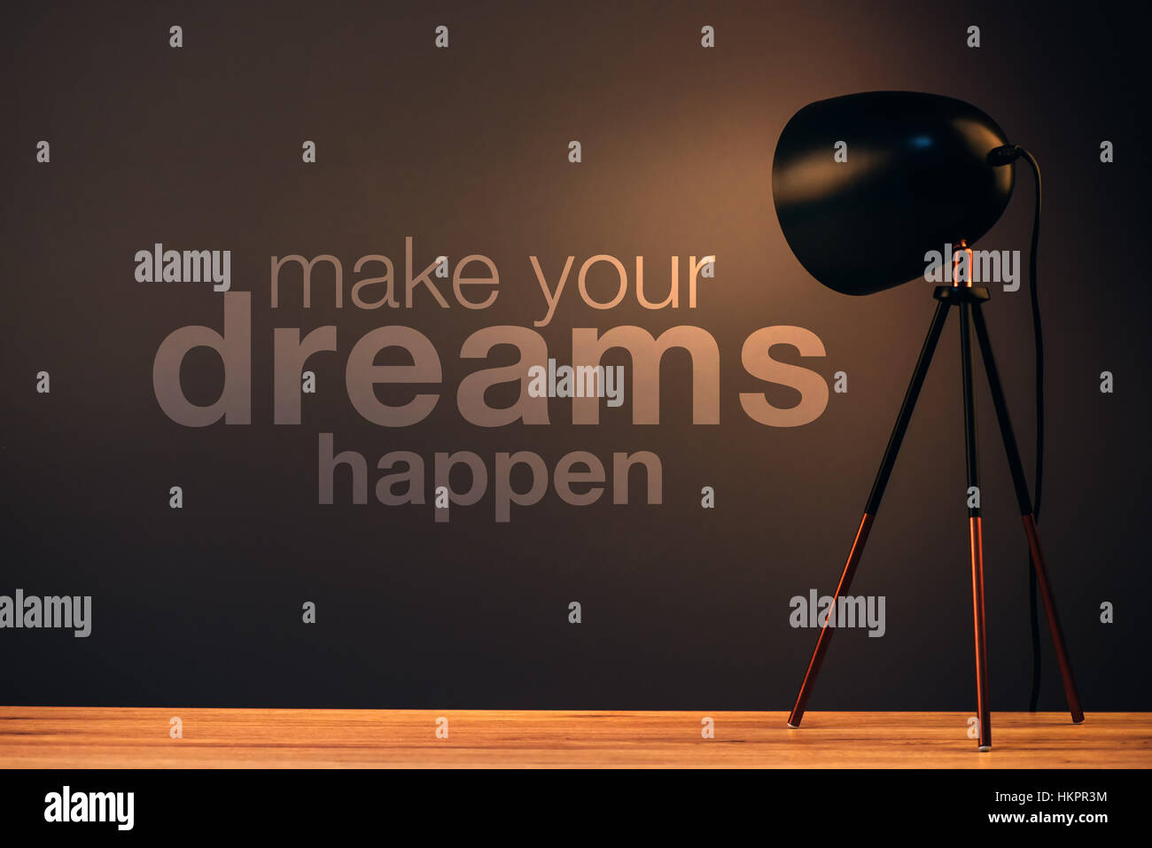 Make your dreams happen, motivational quote on office wall illuminated with desk lamp Stock Photo