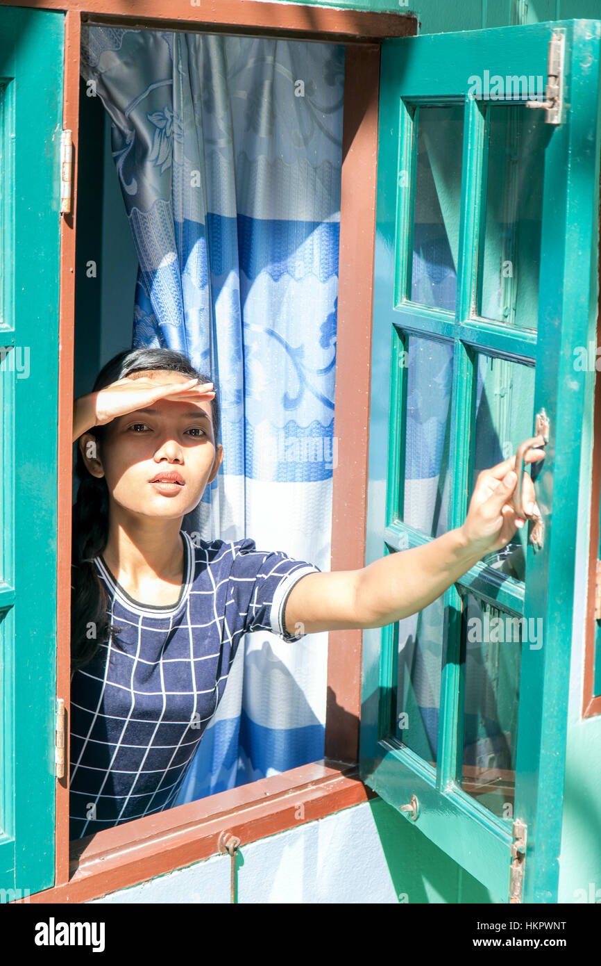 Woman looking through window and covers her face from the sun. A young woman looks out from the wooden window of - Stock Image
