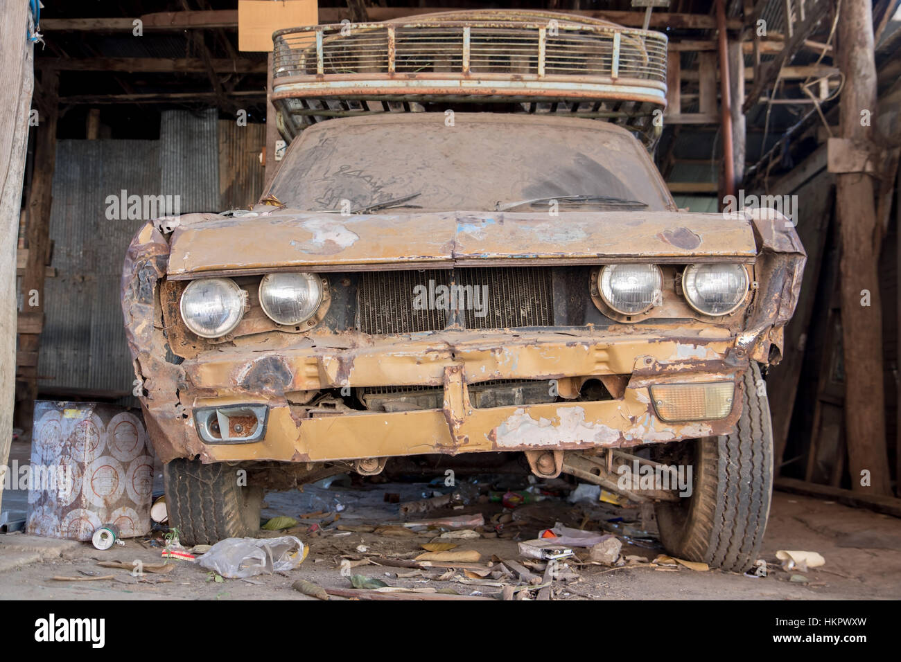 The old dusty car parked in the garage. Broken car, front view. - Stock Image