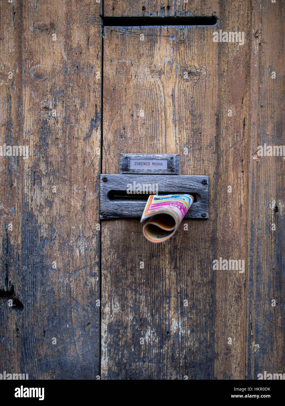 Junk advertising in the letterbox of an old door - Stock Image