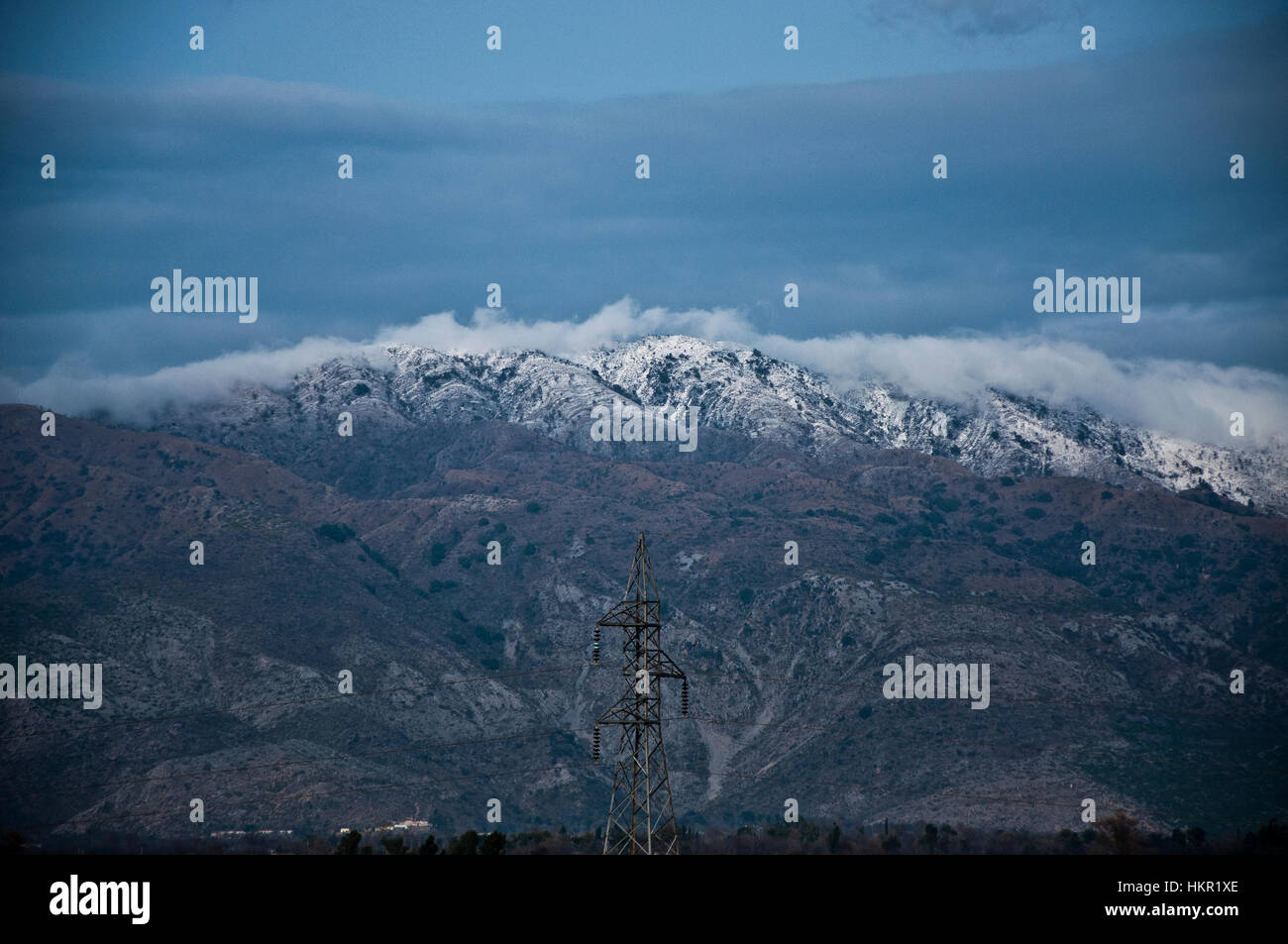 Snowfall on top the cloudy mountain - Stock Image