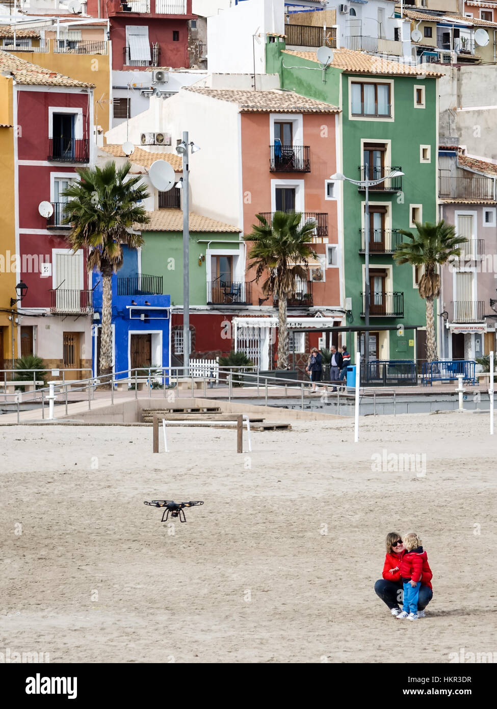 Quadcopter drone flying over a beach in Villajoyosa, Alicante Province, Spain. With mother and child watching. - Stock Image