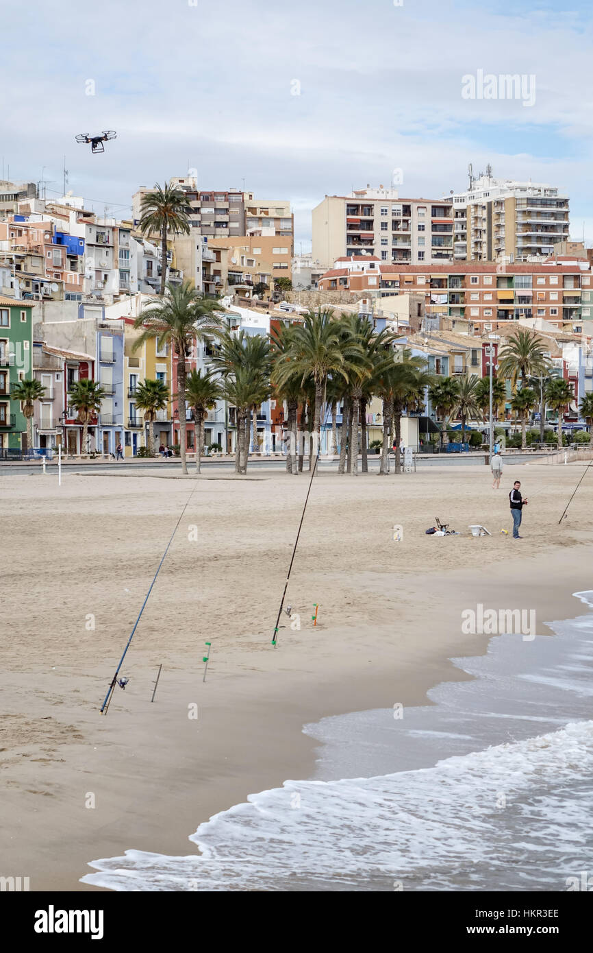 Quadcopter drone flying over a beach in Villajoyosa, Alicante Province, Spain. With fishing poles and fishermen - Stock Image