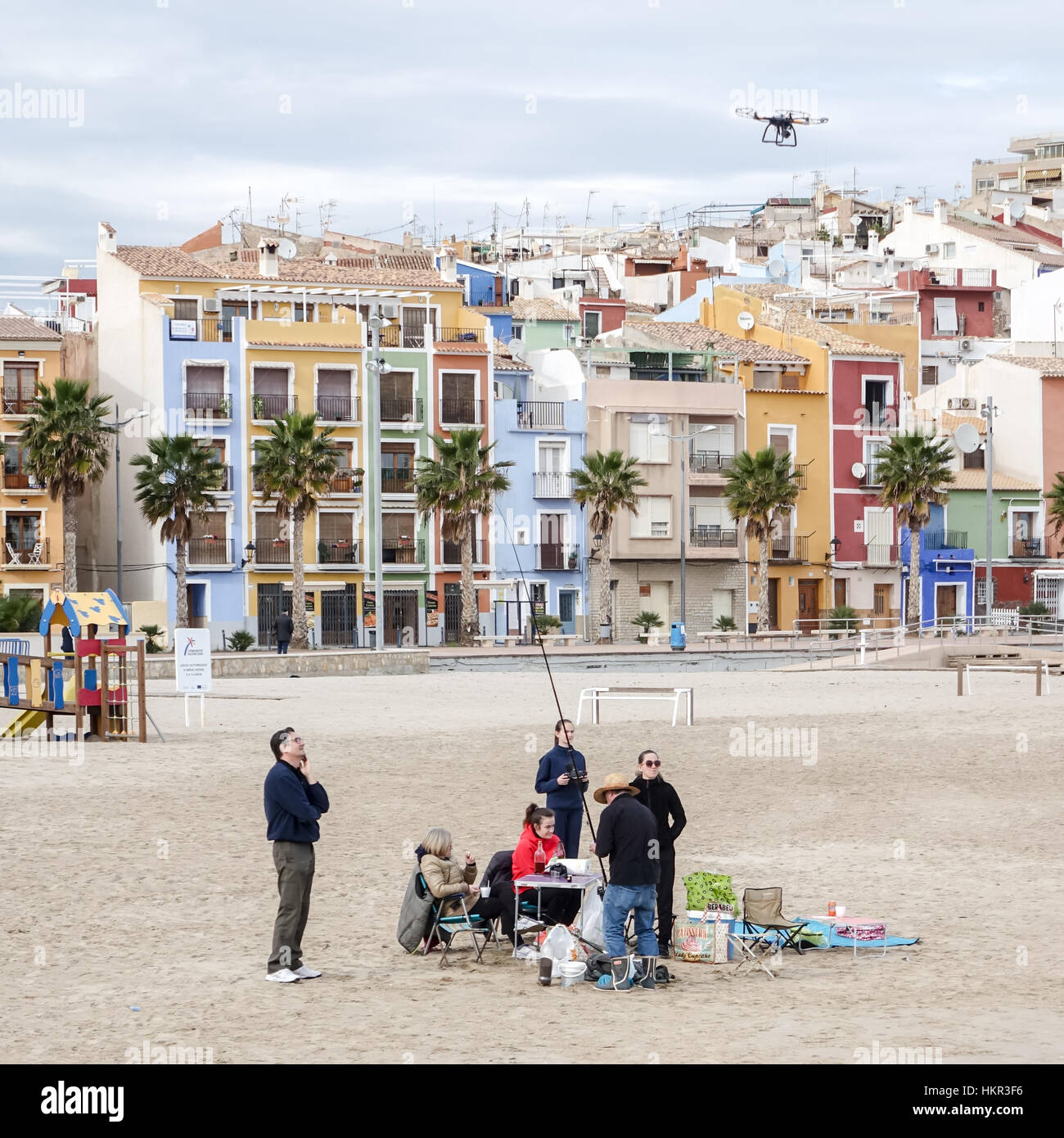 Family fishing on a beach in Villajoyosa, Alicante Province, Spain. Young girl flies quadcopter drone. - Stock Image