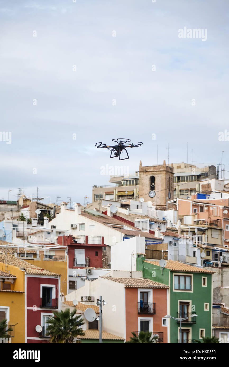 Quadcopter drone flying over a beach in Villajoyosa, Alicante Province, Spain. - Stock Image