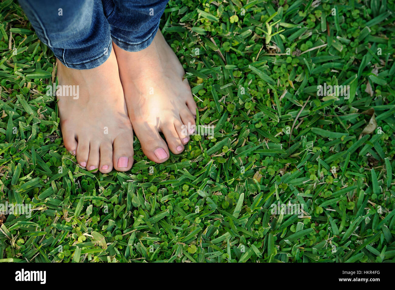 bare foot on jeans stand on green grass - Stock Image