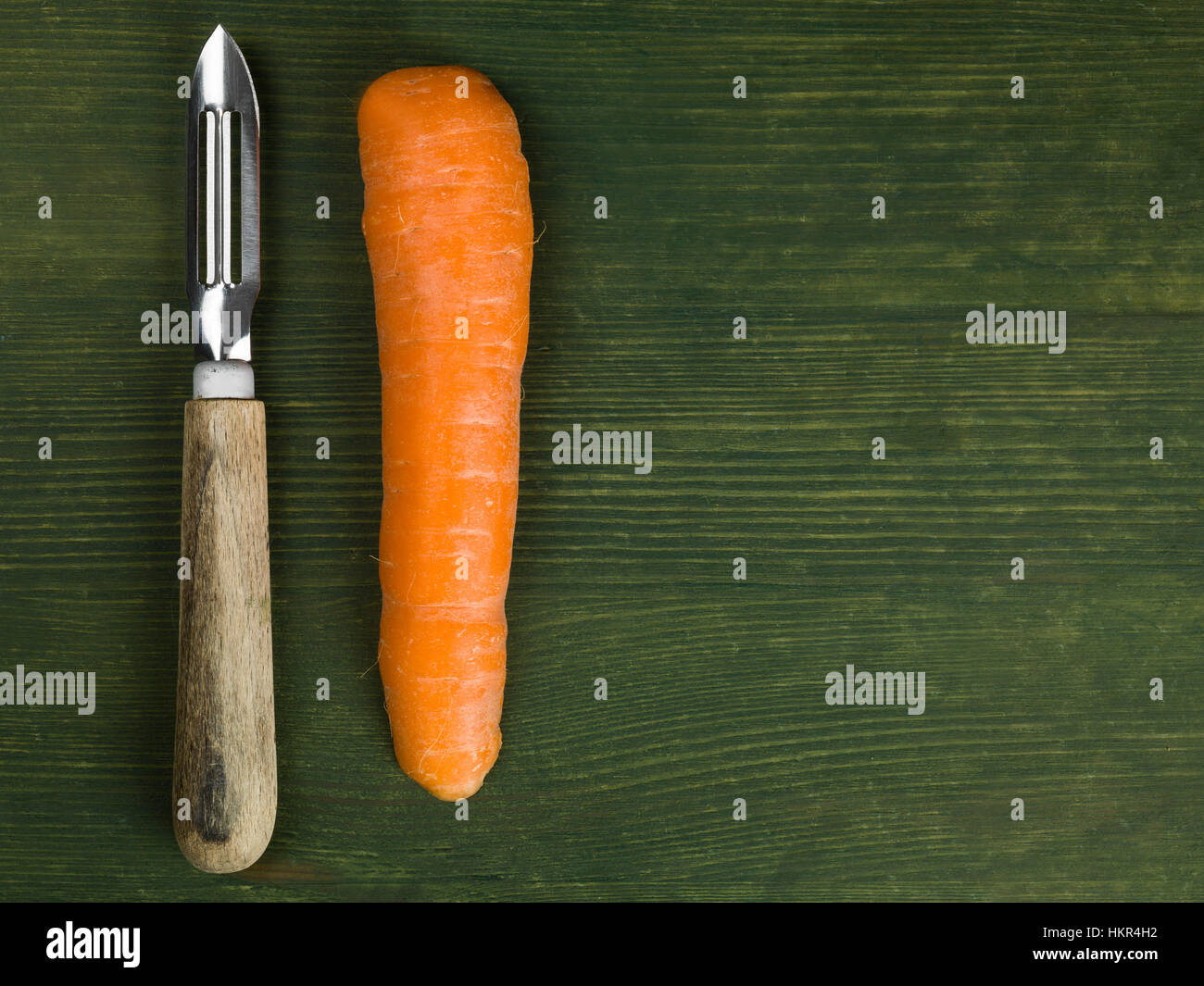 Raw Uncooked Organic Carrots With a Wooden Handled Vegetable Peeler - Stock Image