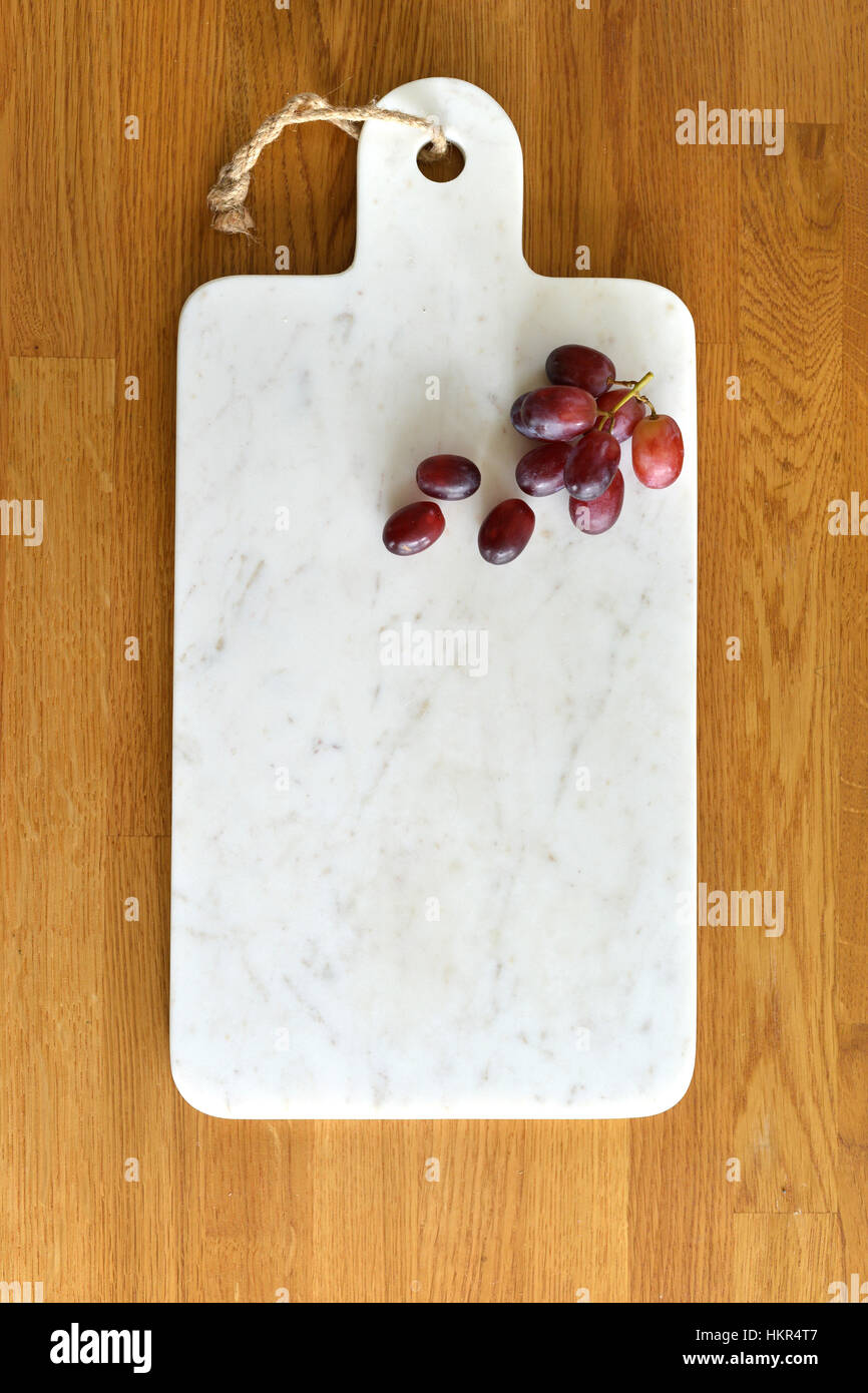 White marble cheese board in a kitchen with cheese and grapes - Stock Image
