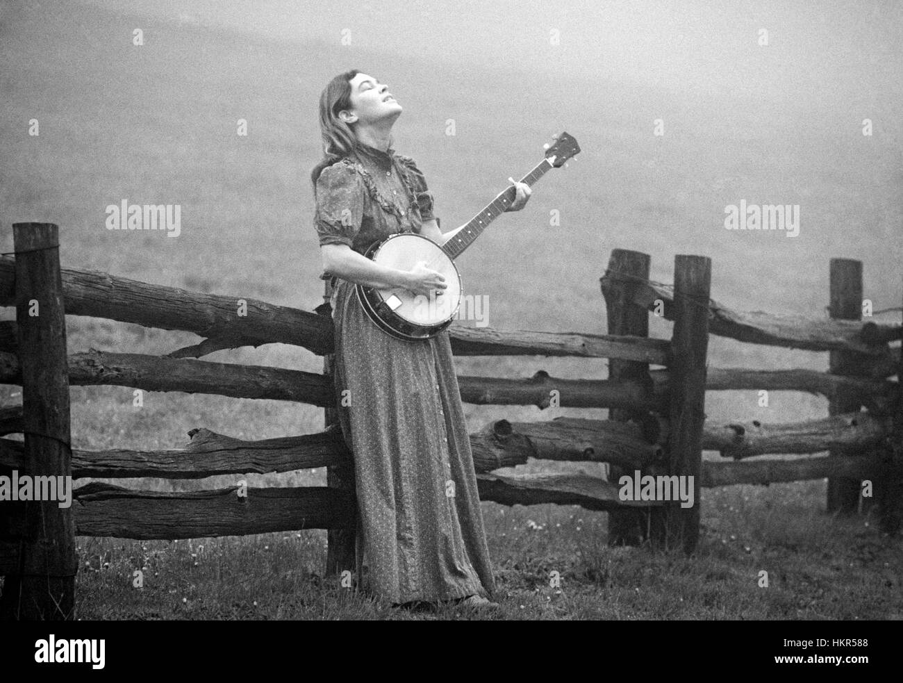 A young woman and her banjo in a misty farm field high in the Blue Ridge Mountains of North Carolina, early morning - Stock Image