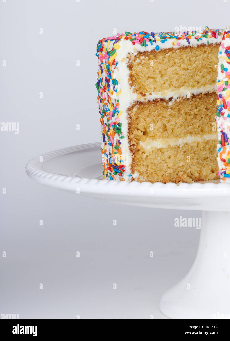White Cake On A Cake Stand Covered In White Frosting And Rainbow