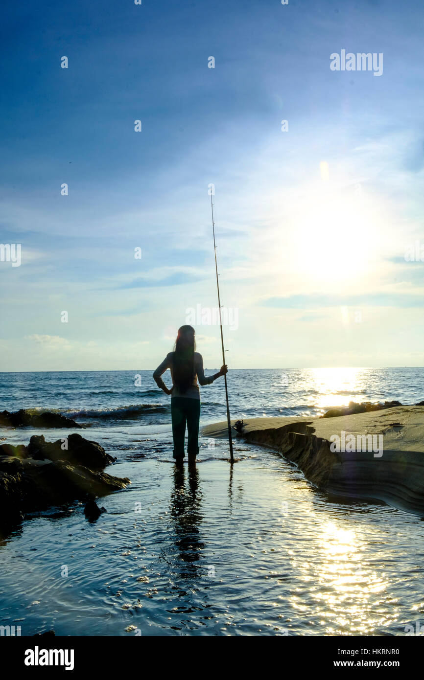 Fisherman with fishing rod silhouetted and standing on a beach - Stock Image