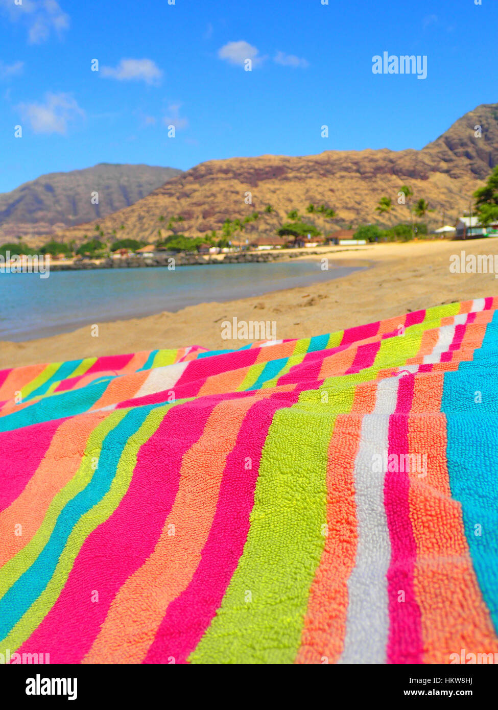 2ec4d3fa23c A brightly colored striped beach towel laying out on a beach at ...