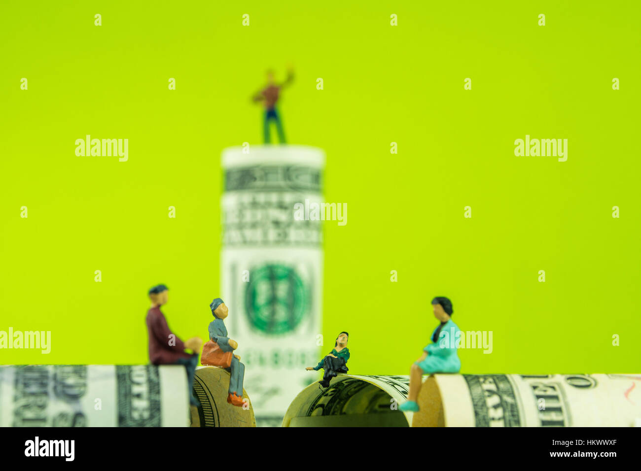 miniature figurines sitting on the edge of 100 dollar banknote with a defocused man standing on dollar bill at the - Stock Image