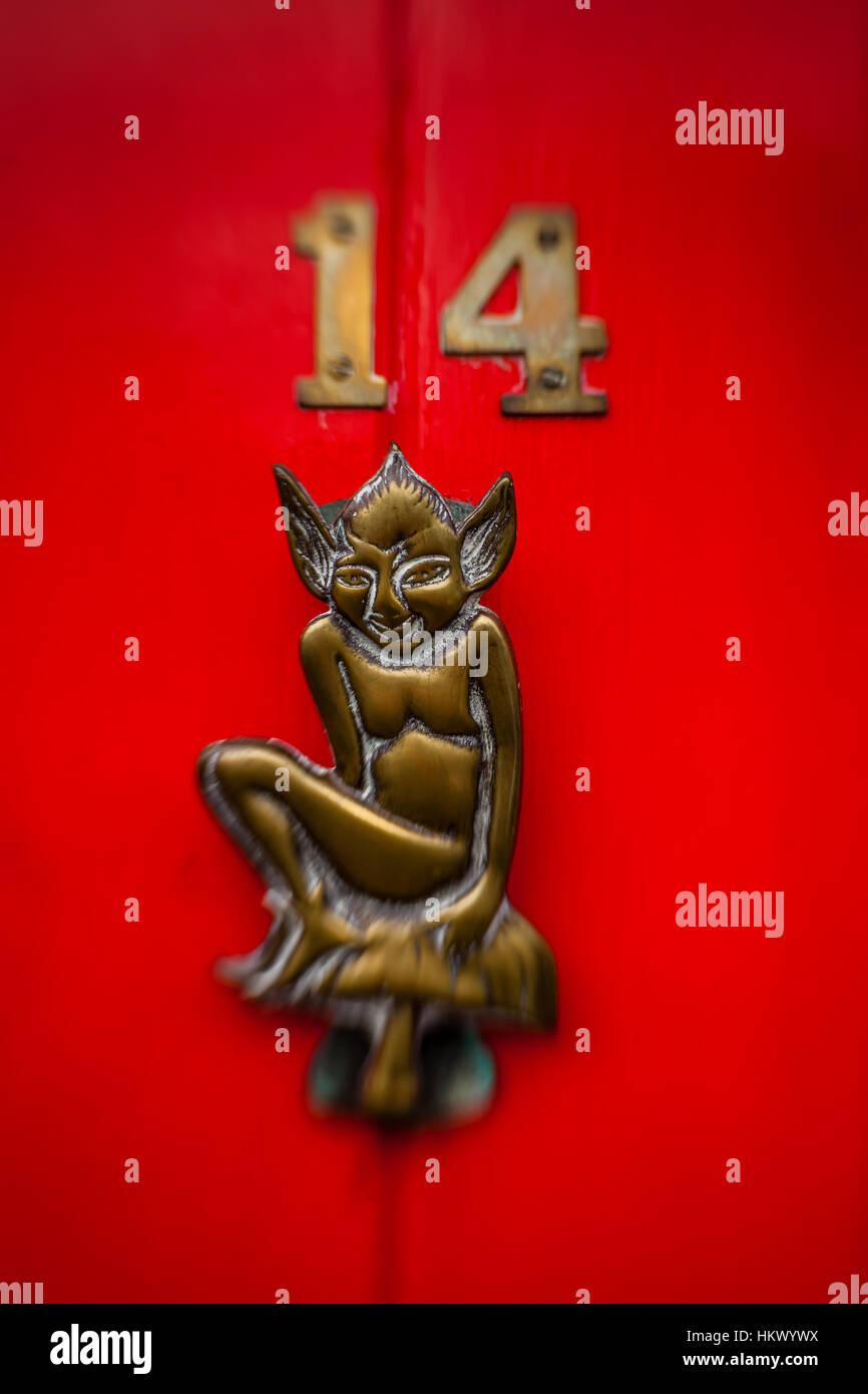 Bronze devilish figure on the red doors - Stock Image