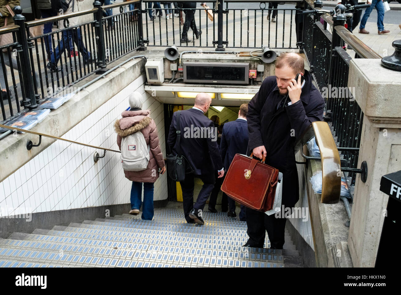 Man holding leather briefcase speaks on mobile phone at entrance to Oxford Circus underground station, London. UK - Stock Image
