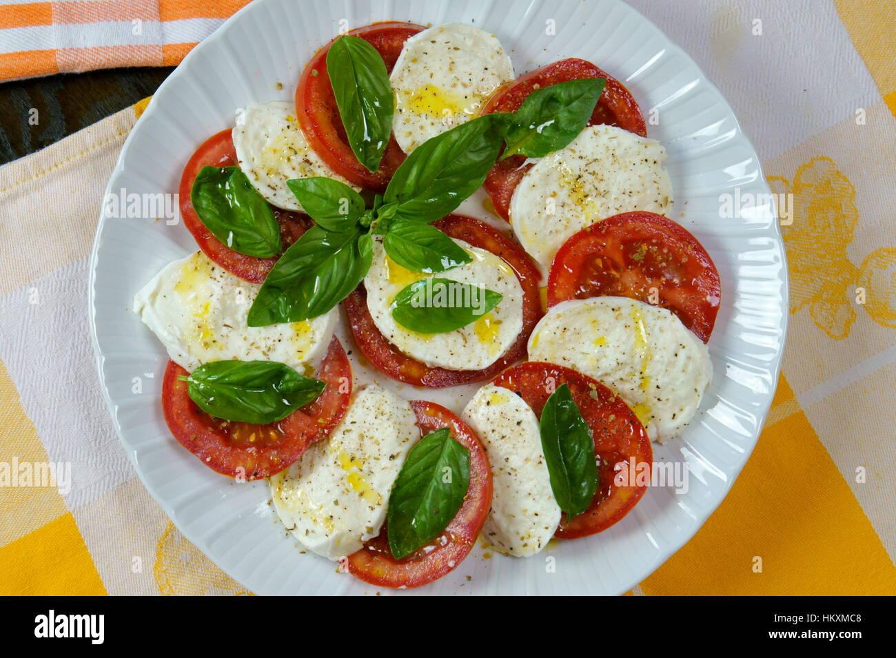 Tomato and buffalo mozzarella Caprese salad on colorful kitchen cloths - Prepared Italian recipe served in white - Stock Image