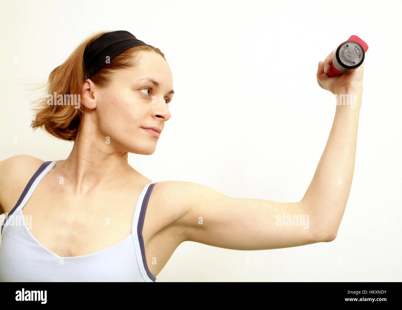 Woman trains with dumbbells - Stock Image