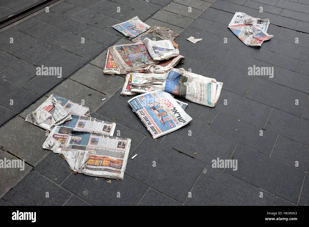 Stack of Israel Hayom national Hebrew language free daily newspaper thrown discarded on the sidewalk in Jerusalem - Stock Image