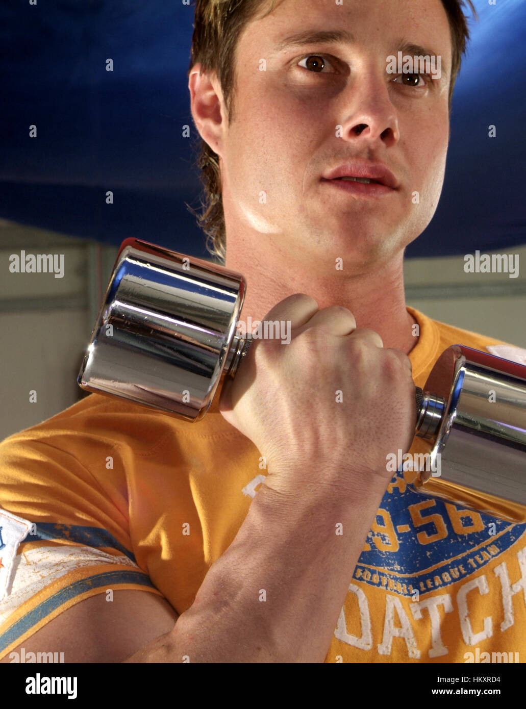 Young man trains with dumbbells - Stock Image