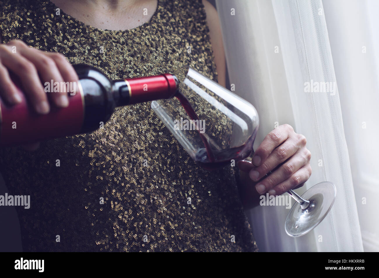 Horizontal close up of Caucasian retro woman in gold sequin vintage dress pouring herself red wine into a tall glass - Stock Image