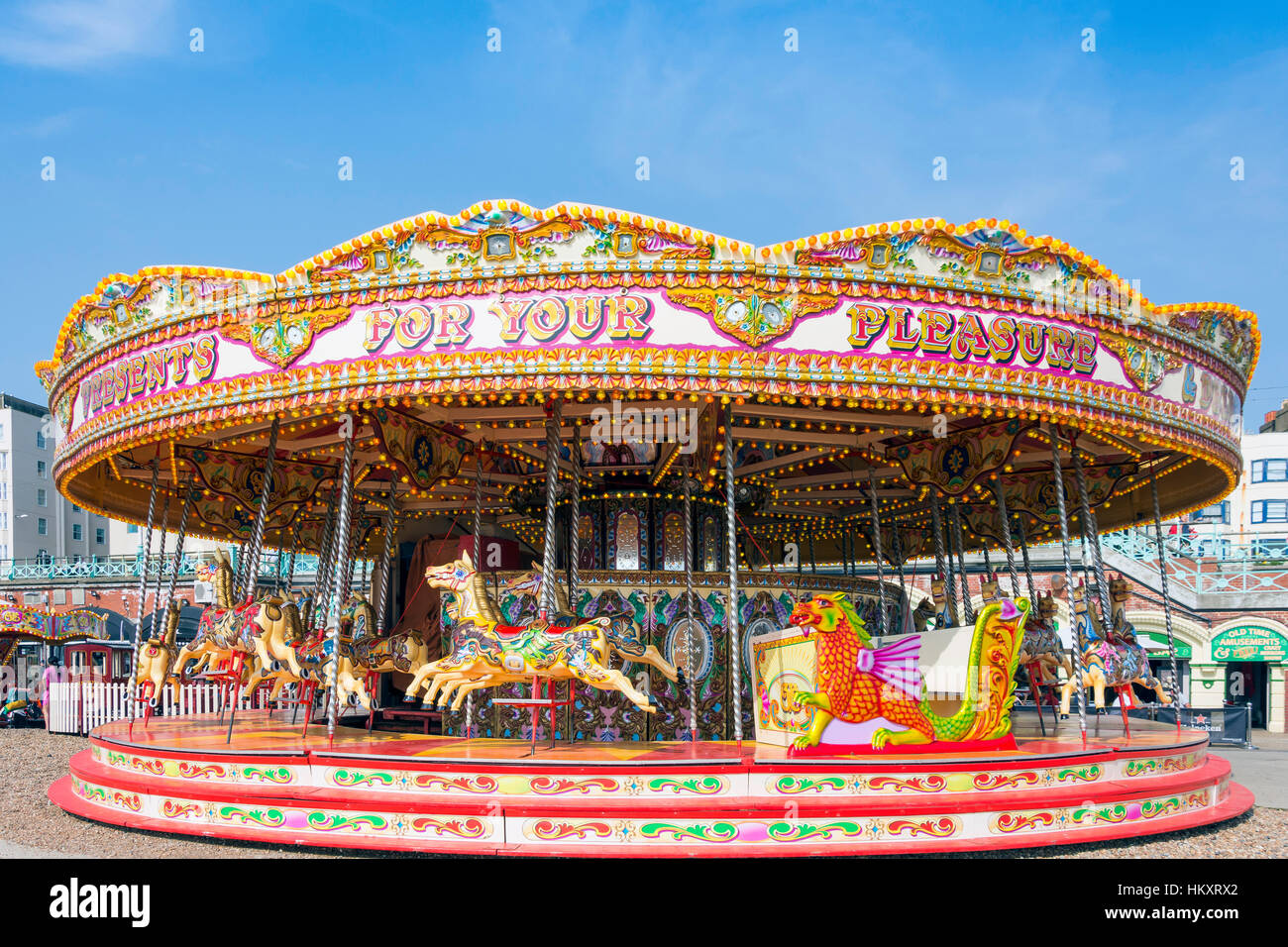 Children's carousel on beach promenade, Brighton, East Sussex, England, United Kingdom - Stock Image