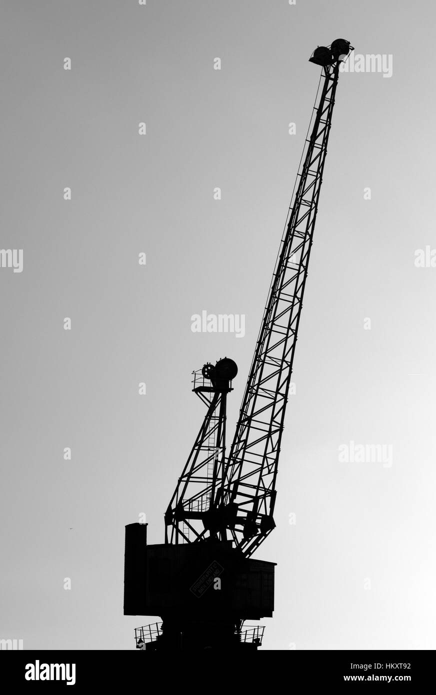 Silhouette of a crane in docklands, London, UK - Stock Image