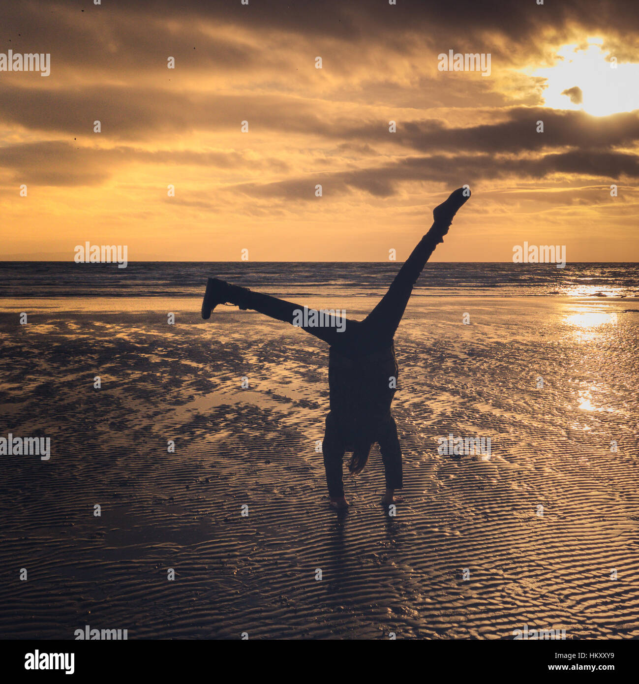 Girl Does A Cartwheel On The Beach At Sunset Stock Photo