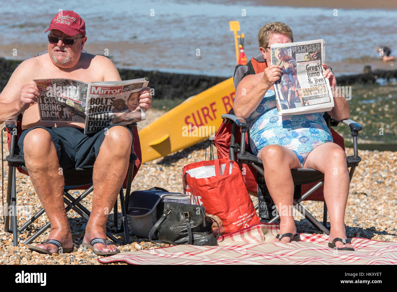 A senior couple sitting on the beach in the sunshine reading their newspapers. - Stock Image