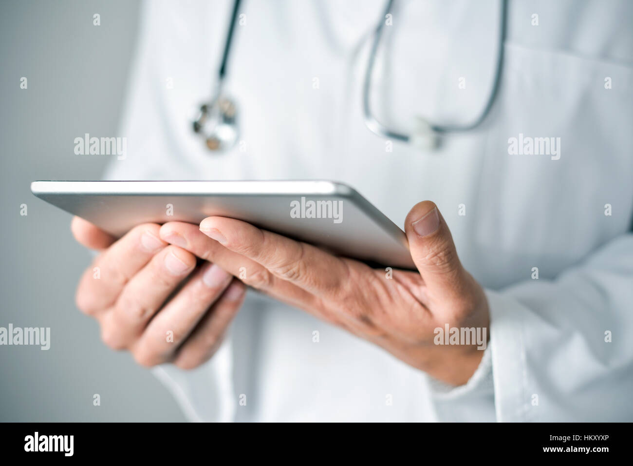 closeup of a young caucasian doctor man wearing a white coat using a tablet computer Stock Photo