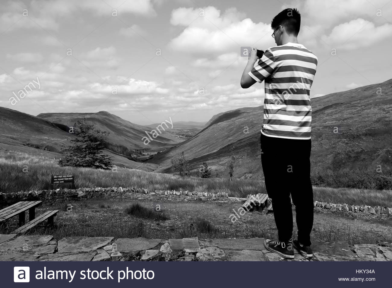 A young man in a green and white shirt takes a photograph of a valley in the West of Ireland - Stock Image