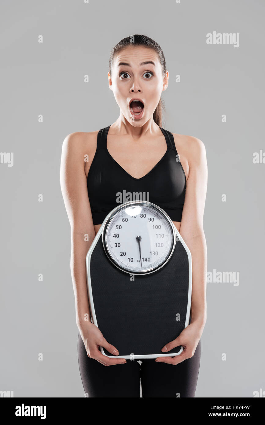 Shocked astonished young woman athlete holding weighing scale over gray background - Stock Image