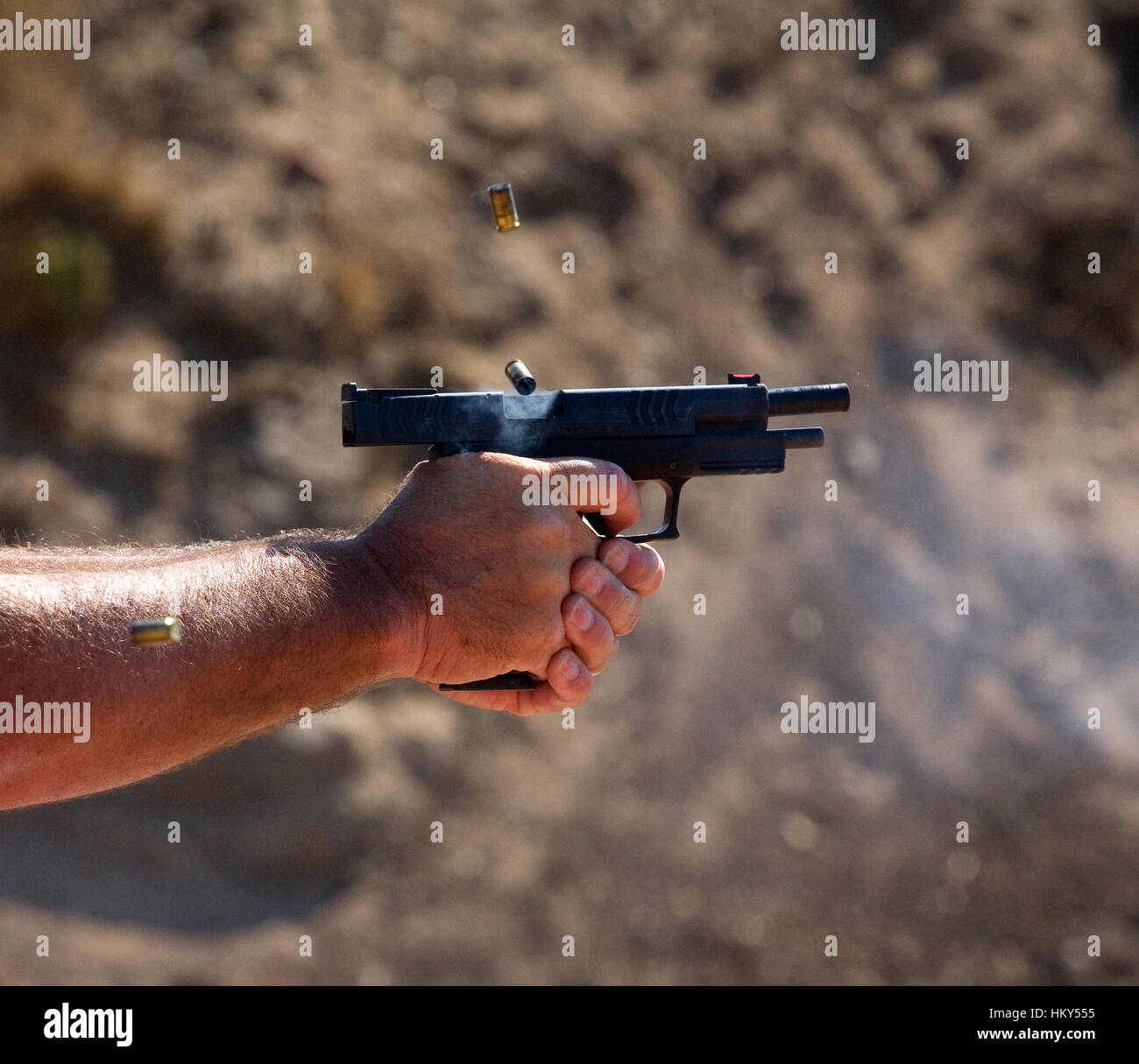 Handgun this is ejecting the third empty shell from fast paced shots - Stock Image