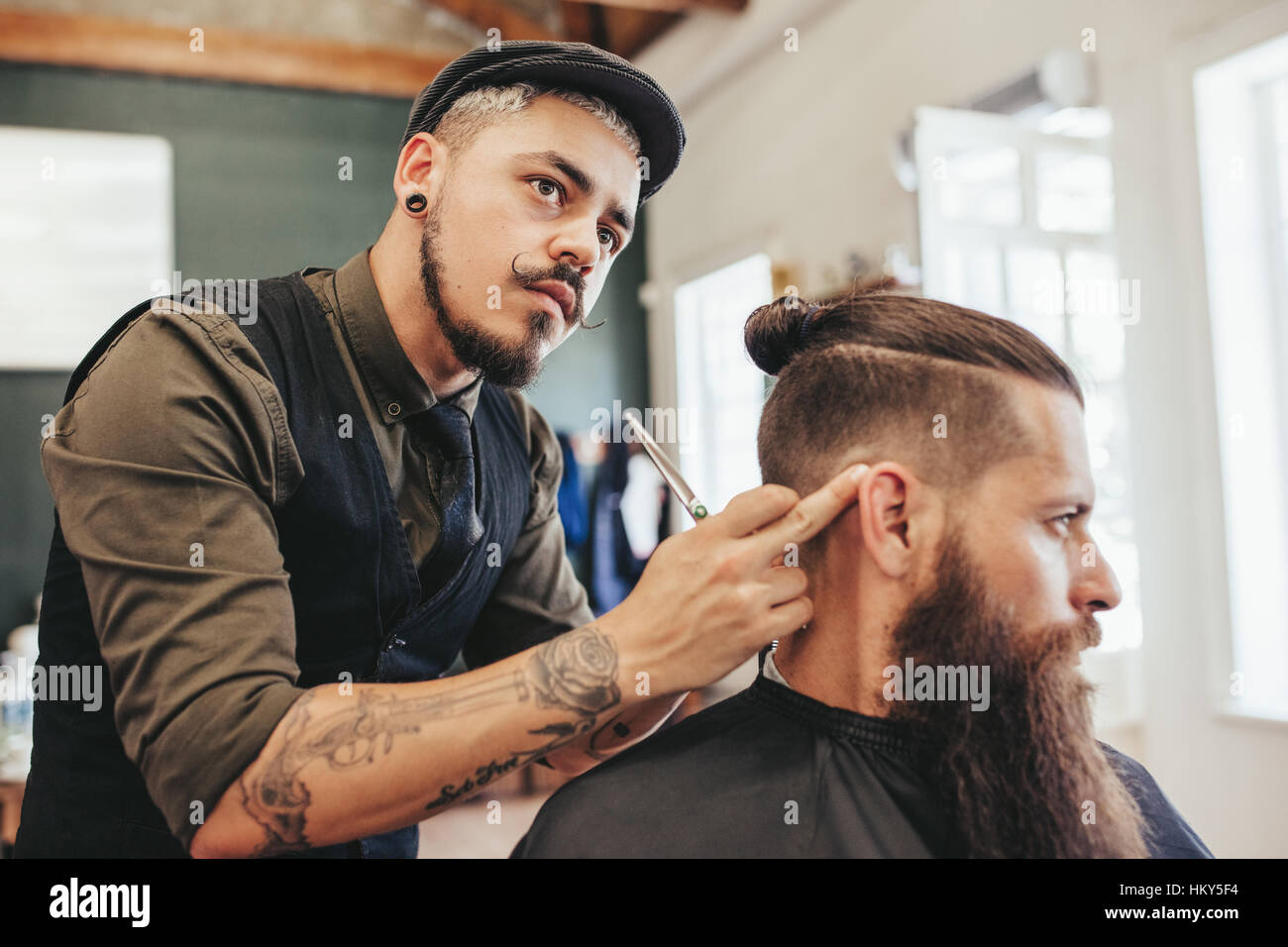 Barber checking symmetry of haircut of his client. Bearded man getting trendy haircut by hairstylist at barbershop - Stock Image